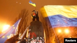 People fly Ukrainian and European Union flags following the toppling by protesters of a statue of Soviet state founder Vladimir Lenin in Kyiv, December 8, 2013.