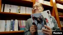 著名香港小说家、香港《明报》创办人查良镛(金庸)在办公室里手持他的著作《书剑恩仇录》。(2002年7月29日)