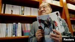 著名香港小说家、香港《明报》创办人查良镛在办公室里手持他的著作《书剑恩仇录》。(2002年7月29日)