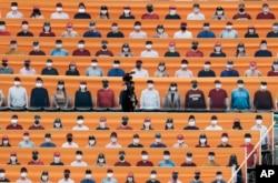 Seorang juru kamera TV berjalan melewati kursi penonton yang penuh dengan penggemar bisbol sebelum dimulainya pertandingan antara Hanwha Eagles dan SK Wyverns di Incheon, Korea Selatan, Selasa, 5 Mei 2020.