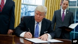 FILE - In this Monday, Jan. 23, 2017, file photo, President Donald Trump signs an executive order to withdraw the U.S. from the 12-nation Trans-Pacific Partnership