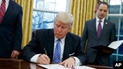 Presiden Donald Trump menandatangani perintah eksekutif untuk menarik AS dari Kerjasama Pakta Perdaganag 12 Negara Trans-Pacific (TPP) di Oval Office Gedung Putih, Washington, 23 Januari 2017. (AP Photo / Evan Vucci, File)