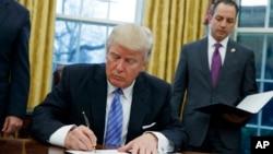 აშშ-ის პრეზიდენტი დონალდ ტრამპი საპრეზიდენტო განკარგულებას აწერს ხელს.