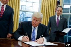 President Donald Trump signs the executive order withdrawing the U.S. from the TPP.