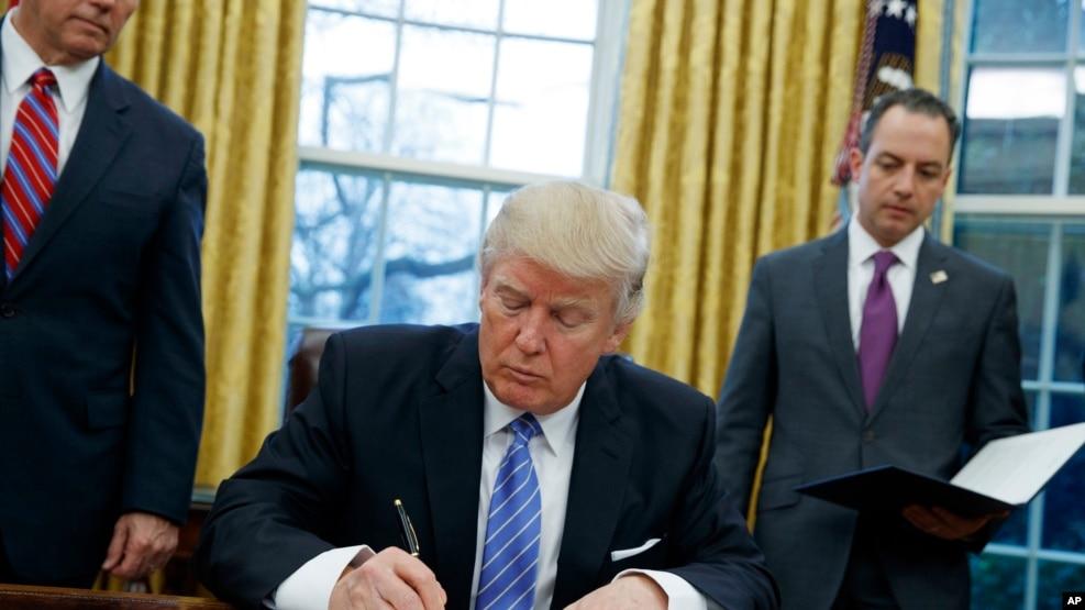 TPP စာခ်ဳပ္မွ အေမရိကန္္ႏုတ္ထြက္ေၾကာင္း အမိန္႔ကို လက္မွတ္ေရးထိုးေနသည့္ သမၼတ Donald Trump ။ ဇန္န၀ါရီ ၂၃၊ ၂၀၁၇။