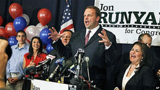 Wife Loretta Runyan, second left, and their son Jon Runyan Jr., left, look on as Republican Jon Runyan gestures while celebrating at his victory party after being elected for New Jersey's 3rd Congressional District, 02 Nov 2010