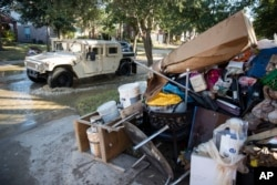 FILE - A military vehicle passes flood-damaged belongings piled on a homeowners' front lawn in the aftermath of Hurricane Harvey at the Canyon Gate community in Katy, Texas, Sept. 7, 2017.