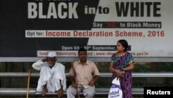 People wait in front of an income tax billboard at a bus stop in New Delhi, India, Sept. 26, 2016.