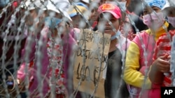 Cambodian garment workers shout slogans behind barbed wire set up by police near the Council of Ministers building during a rally in Phnom Penh, Cambodia, Monday, Dec. 30, 2013. The workers are demanding a raise in their monthly salary from US $160 to $80. (AP Photo/Heng Sinith)