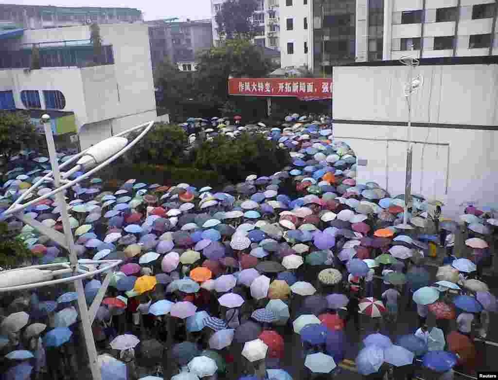 Мешканці міста зібрались перед адміністративною будівлею у Шифангу, провінція Сичуань.