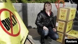 La estudiante Katy Butler posa con las cajas que contienen más de 210 mil firmas para la Asociación Cinematográfica de Estados Unidos (MPAA)