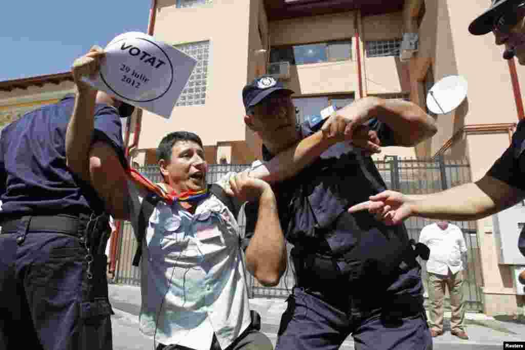 نقل مکان یک معترض توسط پلیس ضد شورش در مقابل ستاد به حالت تعلیق درآمده «ترايان باسسکو»، رئیس جمهوری رومانی، در شهر بخارست. دادگاه قانون اساسی رومانی رفراندوم برای استیضاح باسسکو را رد کرد. اين امر تلاش ها