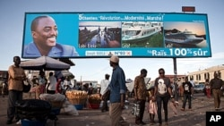 FILE - People walk under a giant poster showing Democratic Republic of the Congo's President and candidate for a second term Joseph Kabila, in Kinshasa, Nov. 7, 2011.