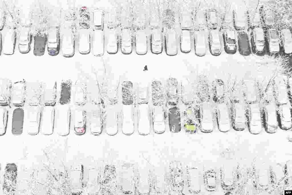 This aerial view shows a pedestrian walking across a parking lot in a residential area after snow fell in Beijing, China.