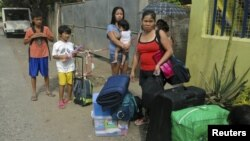 Cư dân chờ xe chở đi sơ tán tại thành phố Cagayan de Oro, miền nam Philippines, ngày 3/12/2012.