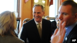 File Photo - South Dakota Gov. Dennis Daugaard greets Secretary of State Shantel Krebs, left, shortly before giving his State of the State address to the South Dakota Legislature, Tuesday, Jan. 12, 2016, at the state Capitol in Pierre, S.D. (AP Photo/James Nord)