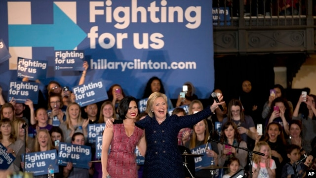 Democratic presidential candidate Hillary Clinton and musician Demi Lovato acknowledge the cheering crowd at a rally on the campus of University of Iowa in Iowa City, Iowa, Jan. 21, 2016.