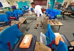 Custodian Jaime Cordona vacuums an empty second-grade classroom at San Marcos Elementary School in Chandler, Arizona, April 26, 2018.