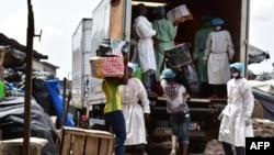 Des employés du ministère de la Santé chargent un camion après avoir vidé les magasins vendant de faux médicaments lors d'un raid au marché d'Adjamé à Abidjan, le 3 mai 2017.