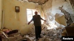 Cư dân làng Pisky đứng trong phòng khách của căn nhà bị hư hại sau các vụ pháo kích ở miền đông Ukraine.