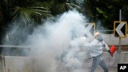 Un manifestante envía de vuelta a la policía una lata de gas lacrimógeno en Hong Kong, el domingo 6 de octubre de 2019. (AP Foto/Vincent Thian)