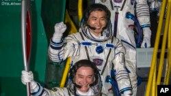 Astronot Jepang Koichi Wakata (tengah), kosmonot Rusia Mikhail Tyurin (membawa obor) dan Astronot AS Rick Mastracchio (atas, tidak terlihat) membawa obor Olimpiade dengan roket Soyuz-FG dari kosmodrome Baikonur, Kazakhstan, menuju ISS (7/11).