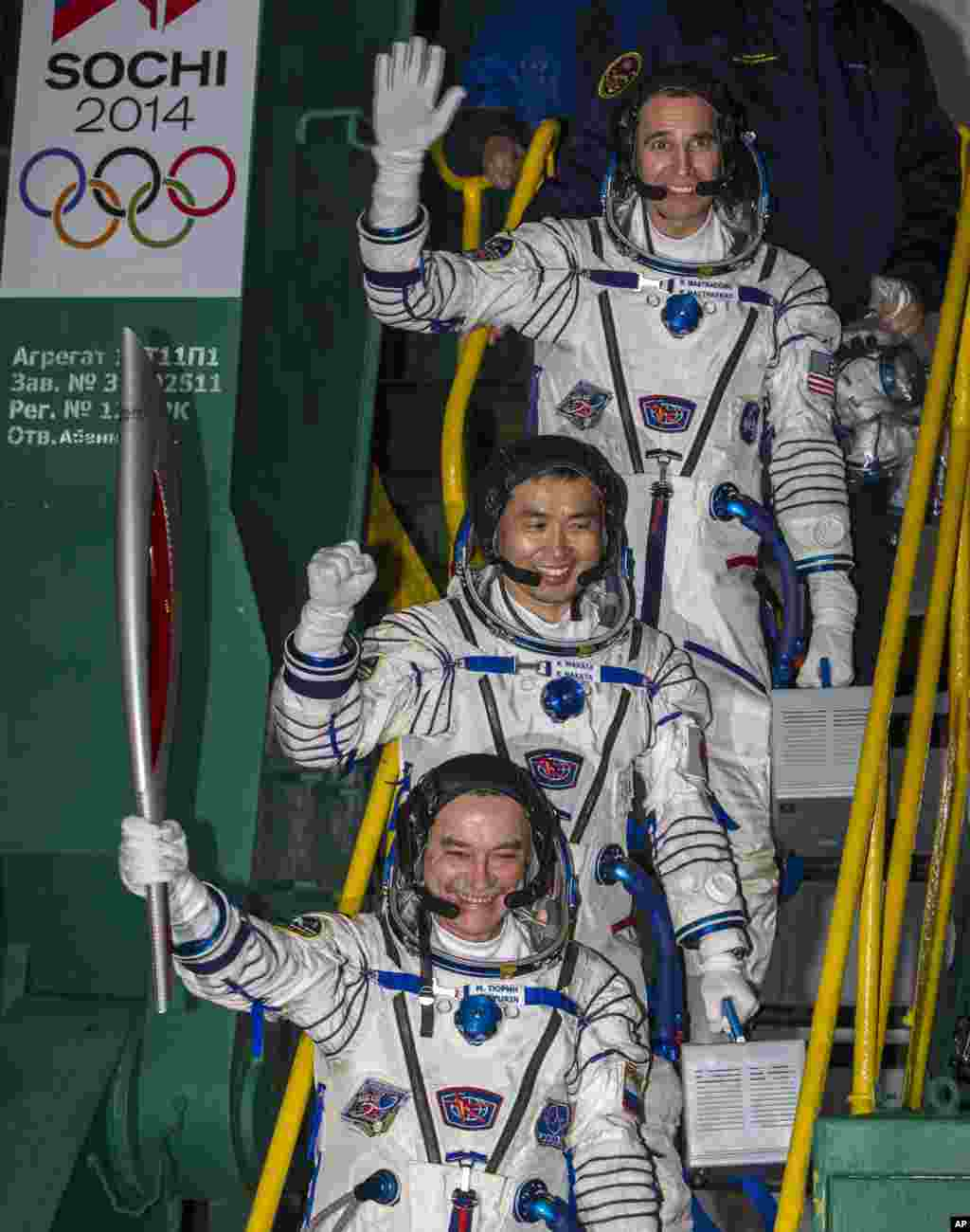 Japanese astronaut Koichi Wakata, center, Russian cosmonaut Mikhail Tyurin, bottom and U.S. astronaut Rick Mastracchio, pose with an Olympic torch prior the launch of Soyuz-FG rocket at the Russian leased Baikonur cosmodrome, Kazakhstan, Nov. 7, 2013.