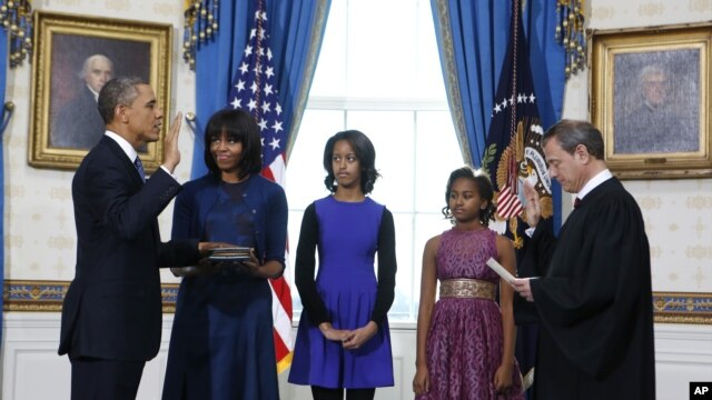 President Barack Obama is officially sworn-in by Chief Justice John Roberts in the Blue Room of the White House during the 57th Presidential Inauguration in Washington, D.C., January 20, 2013. Next to Obama are first lady Michelle Obama, holding the Robin