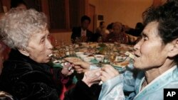20일 금강산에서 열린 남북 이산가족 상봉 행사장에서 한국의 이영실 씨(87)가 북한에 살고 있는 딸 동명숙 씨(66)와 만나 서로에게 음식을 먹여주고 있다.