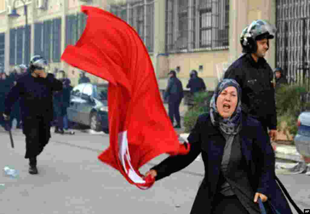 A Tunisian woman waves the national flag in front of the interior ministry during clashes between demonstrators and security forces in Tunis, 14 Jan 2011. Thousands of Tunisians demanded the departure of President Zine El Abidine Ben Ali in marches in the