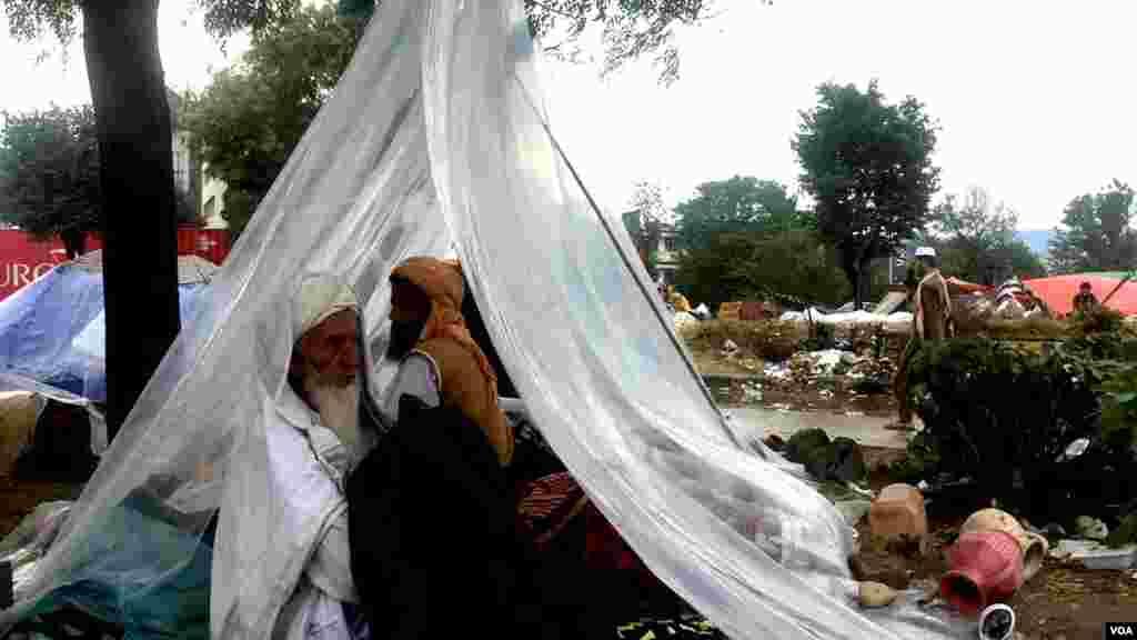 شرکا کی اکثریت نے خود کو بارش سے بچانے کے لیے پلاسٹک کی شیٹیں استعمال کیں۔ دھرنے میں شامل ایک بزرگ اور ان کا ایک ساتھی پلاسٹک کے سائبان تلے بیٹھے ہیں۔