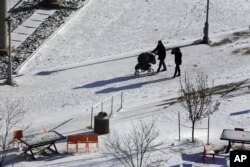 Personas pasean en a nieve en la Plaza Barney Allis, en Kansas City, Missouri, el sábado 19 de enero de 2019.