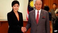 ທ່ານນາງ ຍິ່ງລັກ ຊິນນະວັດ (ຊ້າຍ) ນາຍົກລັດຖະມົນຕີໄທ ຈັບມືກັບ ທ່ານ Najib Razak ນາຍົກລັດຖະມົນຕີມາເລເຊຍ ລຸນຫລັງກອງປະຊຸມຖະແຫລງຂ່າວຮ່ວມກັນ ທີ່ເມືອງ Putrajaya ຂອງມະເລເຊຍ ໃນວັນທີ 28 ກຸມພາ 2013.