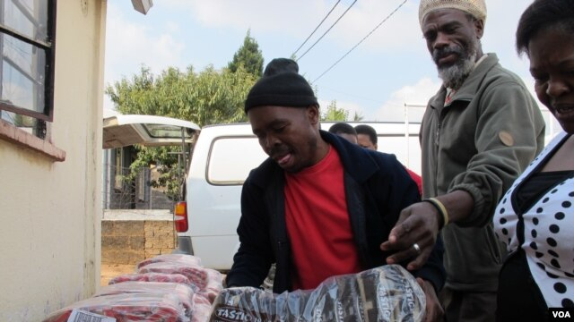 Local Spaza owners distribute products they bought in bulk in Dube Village, Soweto, South Africa (Photo: Gillian Parker for VOA)