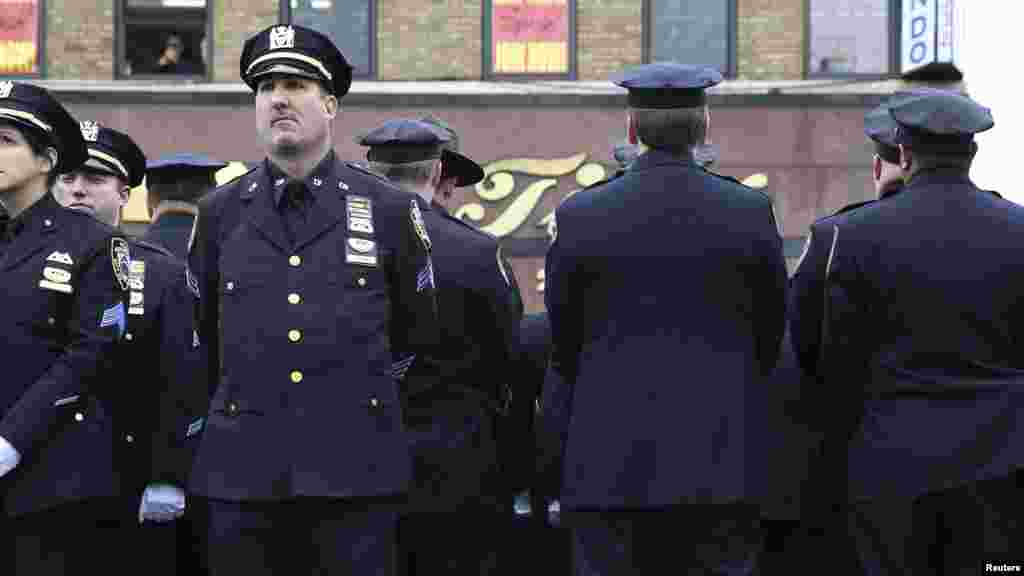 Law enforcement officers stand, with some turning their backs, as New York City Mayor Bill de Blasio speaks on a monitor outside the funeral for NYPD officer Wenjian Liu in the Brooklyn borough of New York, Jan. 4, 2015.