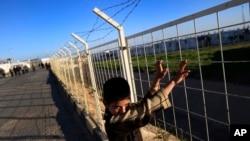 지난 3월 터키 남동부 시리아 접경의 온큐피나 난민촌에서 시리아 난민 어린이가 철책을 만지고 있다. (자료사진)