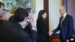 Ukrainian Prime Minister Arseniy Yatsenyuk (r) shakes hands with U.S. Senator Kelly Ayotte in Kyiv, March 23, 2014.