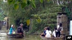 Anak-anak sekolah dan warga menggunakan perahu kecil untuk belewati jalanan di distrik Quang Dien, provinsi Thua Thien Hue, Vietnam Tengah yang tergenang banjir (18/11).