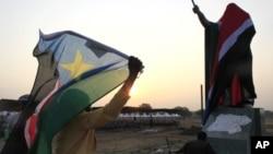 图为一名女子7月9日高举国旗在南苏丹首都朱巴庆祝独立