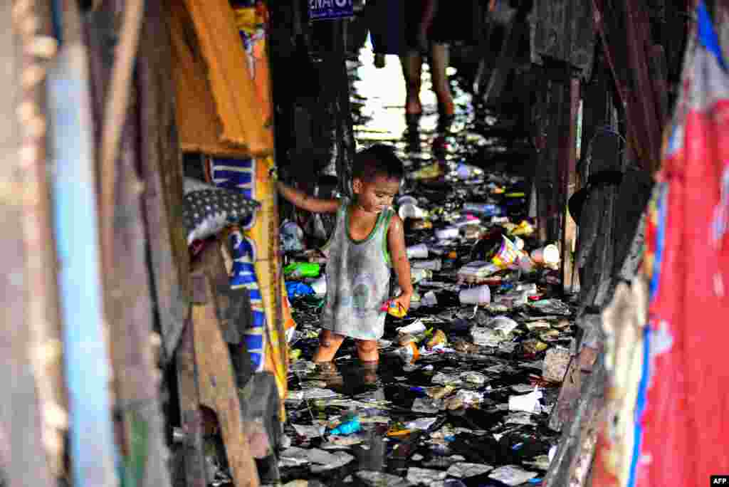 A child wades through the trash filled and polluted waters of a river beside their home in Manila, Philippines, Feb. 29, 2020.