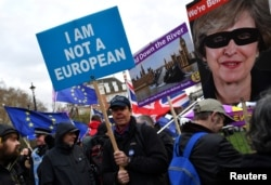A pro-Brexit protester holds up a sign outside the Houses of Parliament in London, Britain, March 14, 2019.