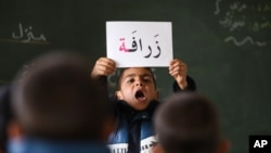 FILE - A Syrian refugee boy holds up a placard in Arabic, during class at a remedial education center run by Relief International in the Zaatari Refugee Camp, near Mafraq, Jordan, Jan. 21, 2016.