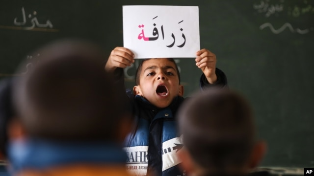 A Syrian refugee boy holds up a placard in Arabic, during class at a remedial education center run by Relief International in the Zaatari Refugee Camp, near Mafraq, Jordan, Jan. 21, 2016.