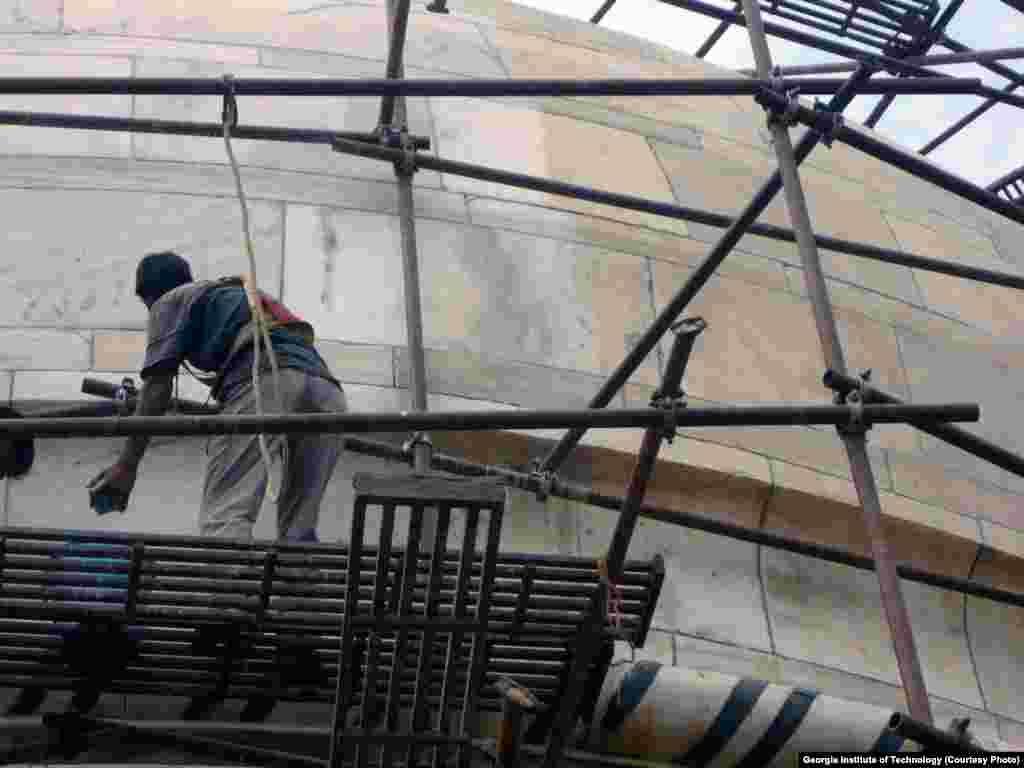 Seorang pekerja membersihkan bagian kompleks Taj Mahal. Marmer di sebelah kanan menunjukkan perubahan warna kecokelatan yang disebabkan oleh partikel-partikel karbon serta debu.