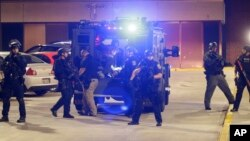 Armed police transport a man to a hospital after he's injured during unrest in Milwaukee, Aug. 14, 2016.
