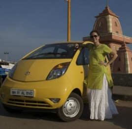 Blogger Vanessa Able stands beside her Tata Nano during her trip across India.