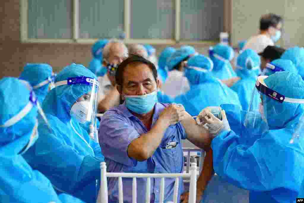 A man, center, receives the AstraZeneca Covid-19 coronavirus vaccine in Hanoi, Vietnam.