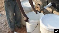 Criança busca água no barril