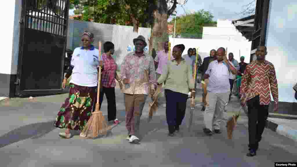 Balai en mai, le président tanzanien John Magufuli, accompagné de quelques autres personnes arrive sur le lieu où est prévu le ramassage d'ordures.