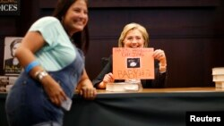 """Former U.S. Secretary of State Hillary Clinton (R) holds a sign given to her by Emily Amilhussin as she signs copies of her book """"Hard Choices"""" in Los Angeles, California June 19, 2014."""